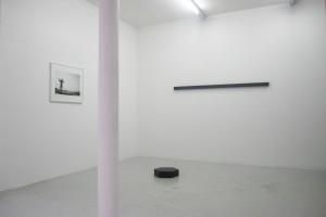 Ananias LÉKI LAGO, « Conakry », 2003, photographie noir et blanc sur papier baryté, 51 x 62 cm / Simon BOUDVIN, « Asphaltes », 2010, goudron – extrait de l'extrémité d'une route –, hexagone de 40 cm, production atelier des Arques